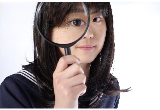 虫眼鏡でのぞく女性の画像