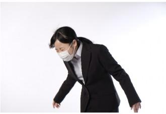 くしゃみをするマスクをつけた女性の画像