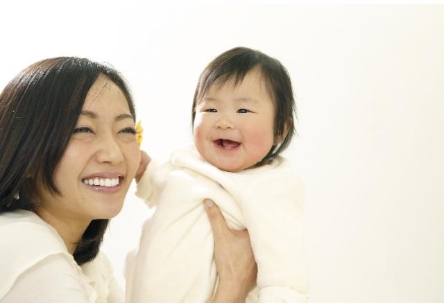 赤ちゃんと一緒に微笑む女性の画像